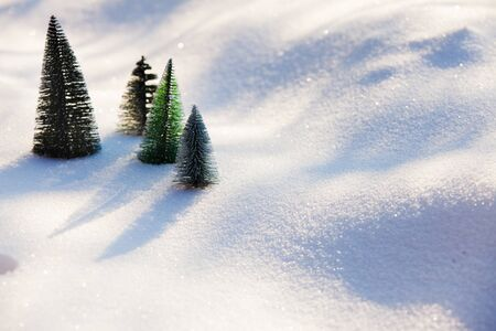 Four small plastic toy christmas trees on the fresh untouched snow with shadows and shapes. Saving nature concept