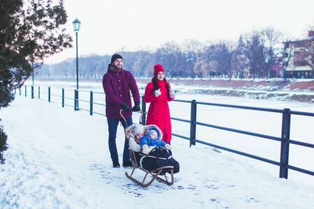 Young attractive father and mother walking together with their small kids, sledding them near winter snowy river in Uzhgorod city, Ukraine