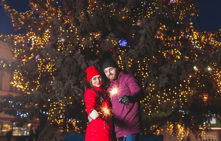 Winter outdoor waist up portrait of young beautiful happy couple posing near city Christmas tree, hugging and holding sparkling bengal lights Reklamní fotografie