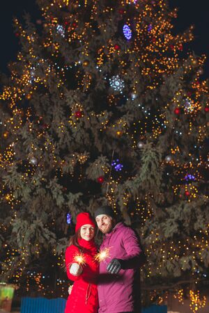 Large decorated Christmas tree with young couple standing near Reklamní fotografie