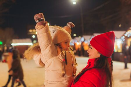 Close view of girl and woman outdoors at winter fair