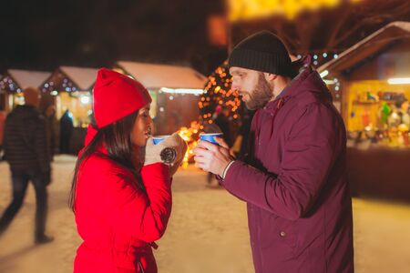 Couple standing oposite each other with mugs at Christmas fair