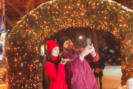 Couple making selfie near decorated arch with lights Reklamní fotografie