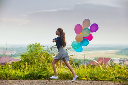 Girl with colorful balloons on the hills