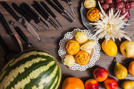 Chinese fruit carving, flat lay hands do it Фото со стока