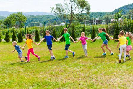 I bambini corrono tenendosi per mano all'aperto. Ragazze e ragazzi si divertono