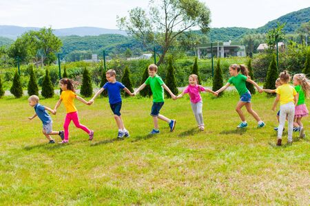Kids run holding hands outdoor. Girls and boys have fun