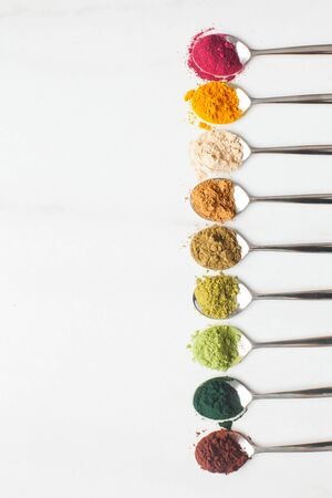 Various types of colorful superfood powders in metal spoons on white table, copy space