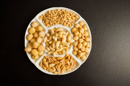 White partitioned dish with variety of nuts