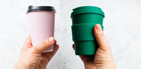 Hands hold paper coffee cup and bamboo reusable drink mug