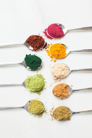 Kitchenware with different colorful superfood powders on wooden table Stock Photo