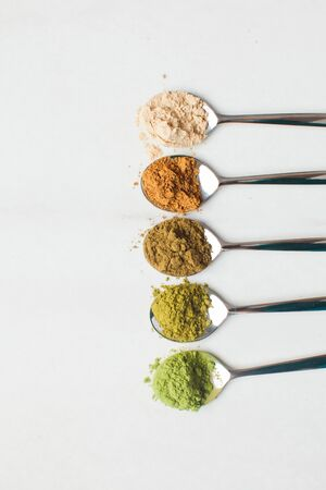 Spoons with different colorful superfood powders on table