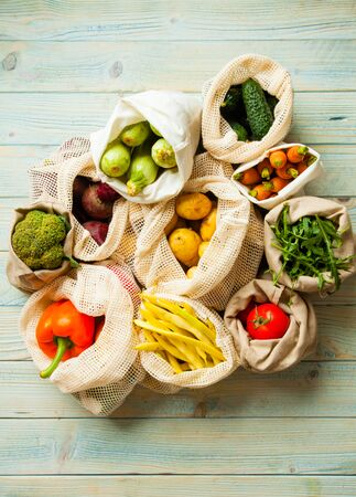 fresh vegetables in eco cotton bags on table