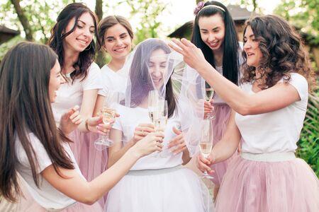 Schöne Brautjungfern um junge Braut mit Schleier
