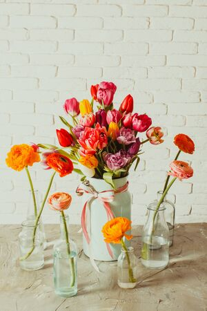 Glass bottles with ranunculus flowers around vase with tulips