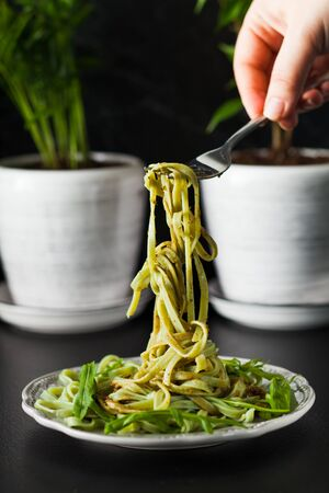 Pasta with arugula and pesto on the plate, black table