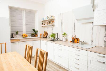 Cucina soleggiata e luminosa con parete in marmo bianco.