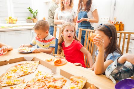 Children eating pizza on the kids party, scandi kitchen
