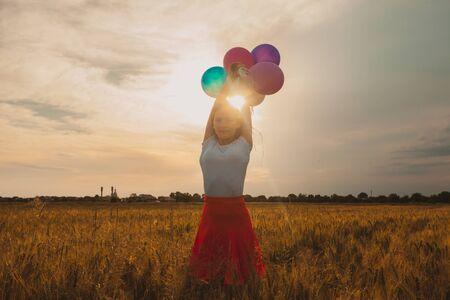 Chica con globos en campo de trigo y sol en la puesta de sol