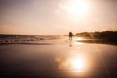 Young romantic couple at the coastline on sunset
