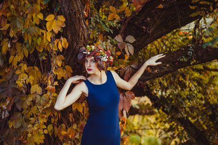 Sensual woman with fall wreath over the autumnal tree 版權商用圖片
