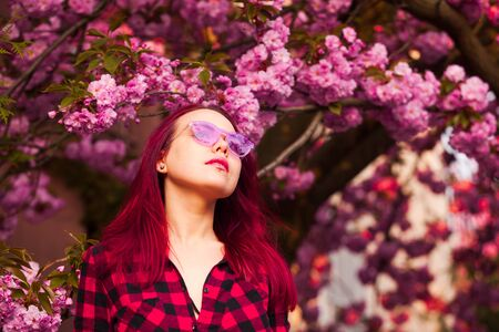 Fantasy Magical Spring Garden and dreamer woman under sakura blossom