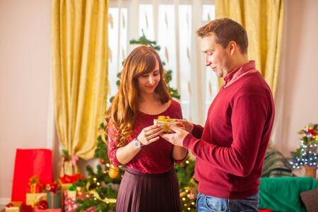 Lovely christmas couple holding presents in the room