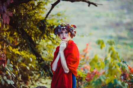 Sensual woman in wreath over the autumnal tree
