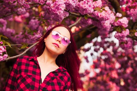 Girl in pink glasses with long pink blowing hair.
