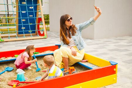 Mother sitting with son in sandbox and making selfie Foto de archivo - 132031098