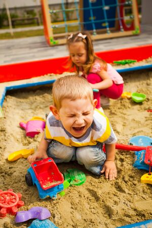 Crying unhappy boy play with car in sandbox Stock Photo