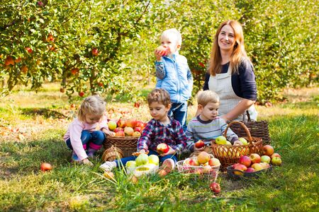Teacher with preschoolers in the apple garden
