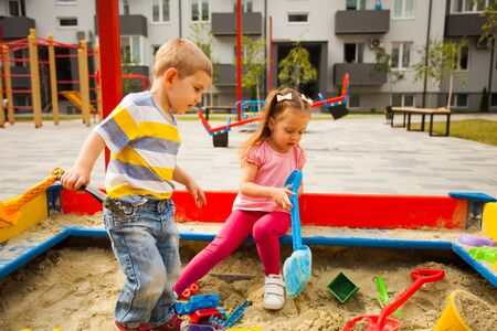 Two cute little twins playing in a sandbox