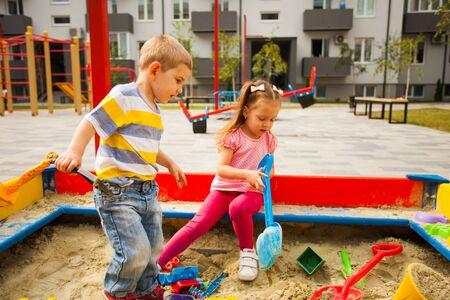 Zwei süße kleine Zwillinge, die in einem Sandkasten spielen