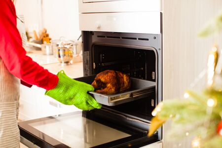 Mother getting turkey out of oven for celebrate christmas holidays together at home.