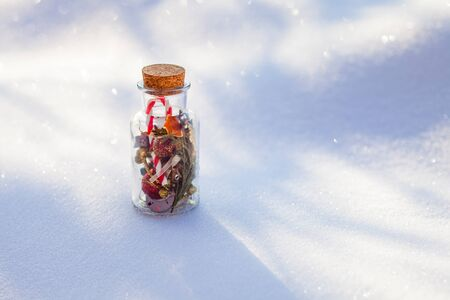 Vintage bottle with Christmas holiday attributes on the snow in the forest
