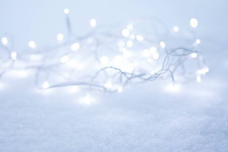 White bokeh lights defocused at the background, laying on the snow frost. Winter and holiday background