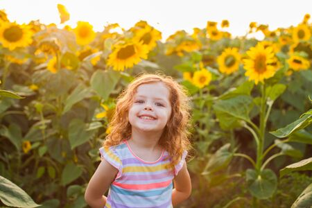 Smiling pretty little girl on sunflowers field background. Happy summer holidays