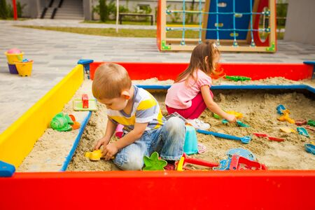 Happy kids playing with sand at playground. Outdoors creative activities for kids. Reklamní fotografie