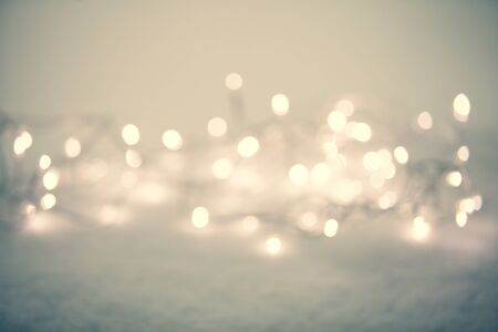 Christmas lights liying on the snow outdoors. Defocused abstract winter background for holiday Stok Fotoğraf