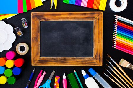 Retro wooden chalkboard between school stationery flat lay. Place for text - back to school concept 版權商用圖片