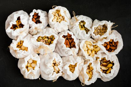Eco pouches with various types of nuts on black background.