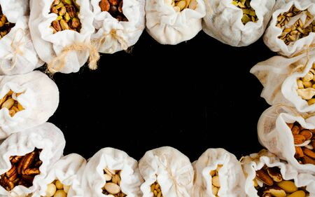 Eco textile bags with various types of nuts on black background, top view, copy space. Stok Fotoğraf