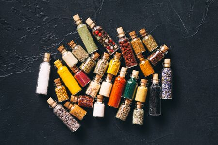 Art of food. Assorted ground spices in vintage bottles on black concrete background. Scattered bottles top view, aroma souvenirs