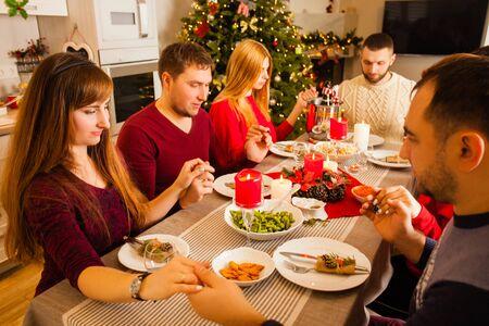 Familiares y amigos jóvenes rezando y bendiciendo la mesa en el comedor navideño