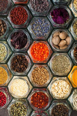 Assorted colorful spices and herbs in bottles, top view