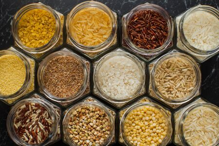 Top view of glass jars with various cereals, rice, couscous, bulgur, and buckwheat. Clean eating concept