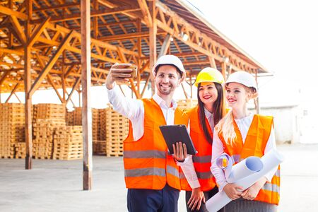 Smiling engineers taking selfie at contruction site