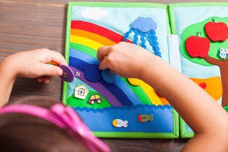 Vista dall'alto della ragazza che sta disponendo i cerchi per i colori dell'arcobaleno nel libro tranquillo