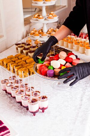 Catering bar for celebration. Colorful macaroons on a plate. Tasty desserts served on the sweet table